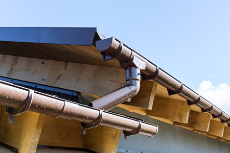 Rain gutter system on a roof of home against blue sky