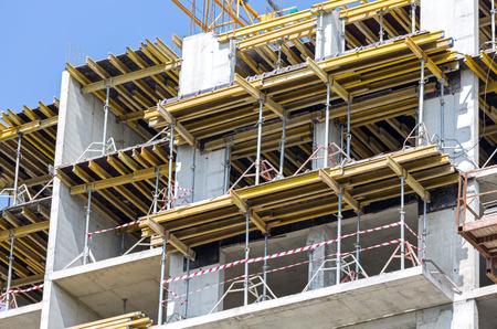 construction equipment: Concrete building construction site against dark blue sky