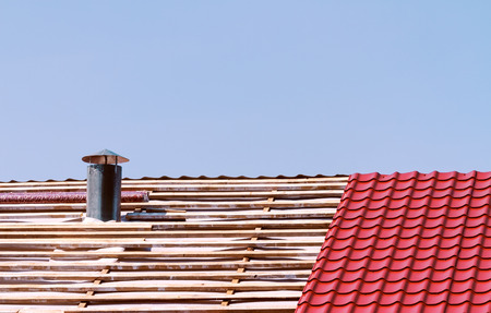 smokestack: New metallic tiled roof with smokestack under construсtion