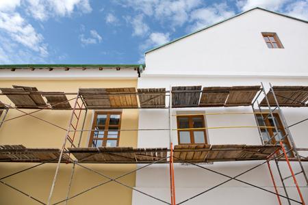 renovate old building facade: Scaffolding covering a facade of an old building  under renovation Stock Photo