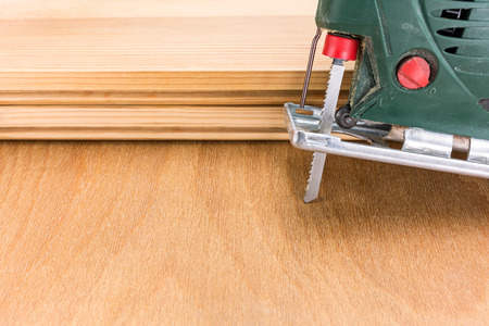 Green electric fret-saw tool on wooden background with planks