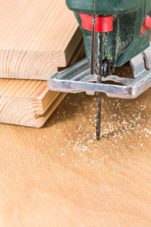 fret: Wood planks cutting with electric fret saw tool