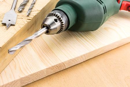 screw driver: Closeup electric screw driver on wooden floor
