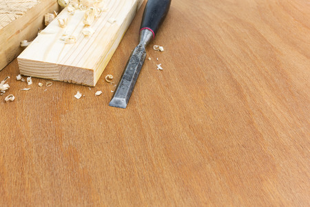 Old carpenter wood chisel tool with boards and shavings