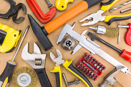 Set of assorted working tools on wooden background photo