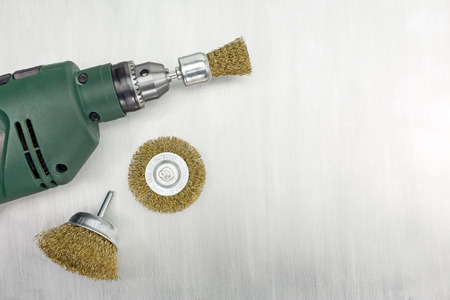 tool chuck: Electric drill and rotating metal brushes on scratched background