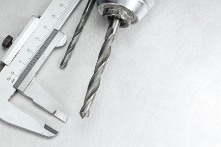 vernier caliper: Electric drill head with drill bits and vernier caliper on scratched metal background