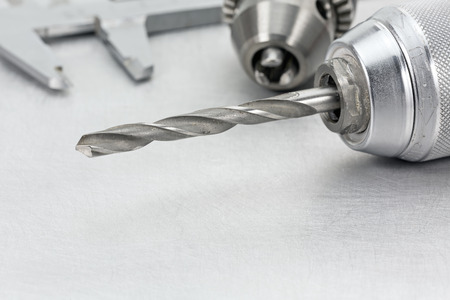 borer: Electric drill chuck with drill bits and vernier caliper on metal background Stock Photo