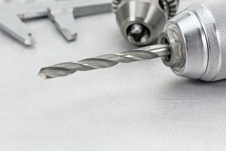 vernier caliper: Electric drill chuck with drill bits and vernier caliper on metal background Stock Photo