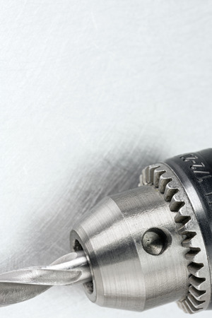 bit background: Electric drill head with drill bit on scratched metal background