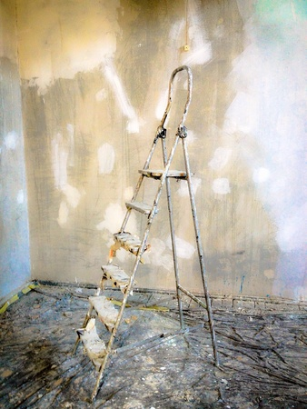 step ladder: Home improvement. Dirty step ladder against grunge plaster wall Stock Photo
