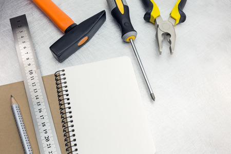 standard steel: Set of tools on metal background with notepad