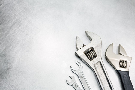 industrial equipment: Set of spanners and wrenches on scratched metal background Stock Photo