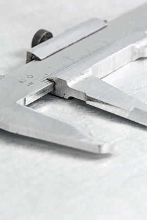 caliper: Stainless steel vernier caliper on scratched metal background Stock Photo