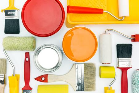 charolas: diversas herramientas de pintura y accesorios para rehabilitación de viviendas en el fondo blanco Foto de archivo