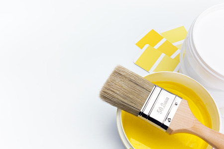 newly opened can of yellow paint and brush with color guide on white background
