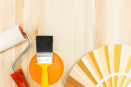brush and roller with color guide and paint can on wooden background photo