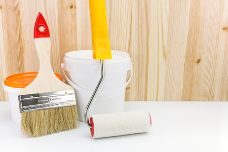 paint roller with brush and paint can against wooden boards photo