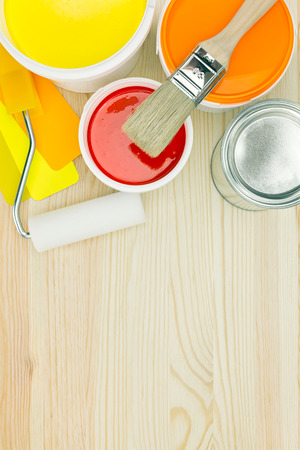 painting and decorating: opened paint cans brush roller and color samples on wooden background