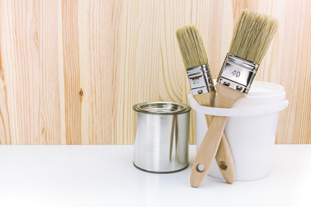 paint cans: paintbrushes with paint cans against wooden background