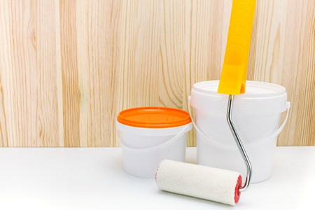 paint cans: paint cans and roller for home renovation against wooden background