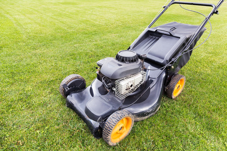 lawn mover cutting green grass on garden field photo