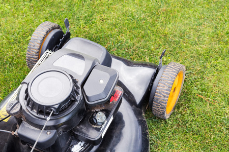 top view of lawn mower on green grass photo