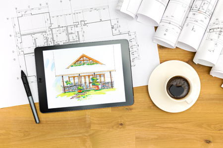 blueprint: tablet coffee cup and architectural blueprints on working table