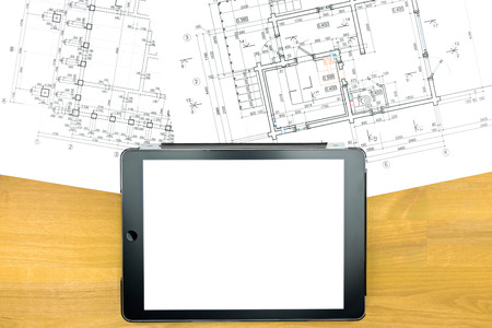 blank digital tablet and construction plans on wooden table