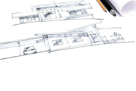 paper rolls: architect crayon sketches of a new house with pencils and paper rolls next to it