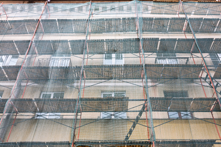 old building facade: old building facade under construction with green protective net Stock Photo