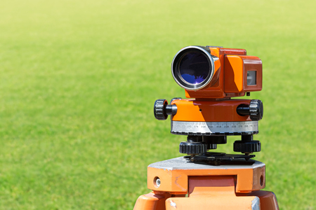 geodetic: optical level mounted on tripod at construction site