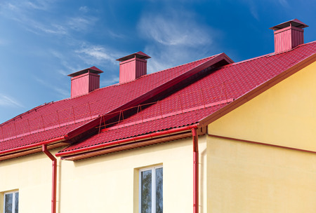 chimney corner: new red roof of new house with chimney against blue sky Stock Photo