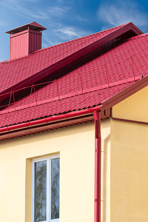 chimney corner: new red tiled roof with chimney and rain gutter Stock Photo