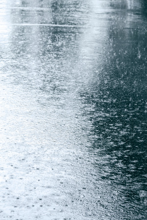 downpour: wet asphalt with raindrops in a puddle and reflections Stock Photo