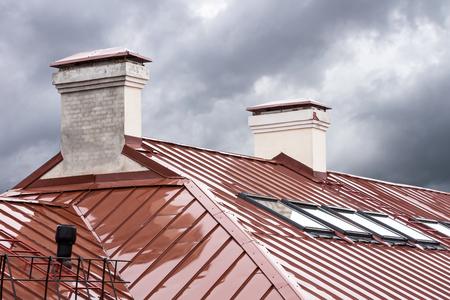 nuevo techo de metal rojo con tragaluces y chimeneas