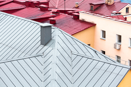 chimney corner: top view on colored metal roofs of the old city
