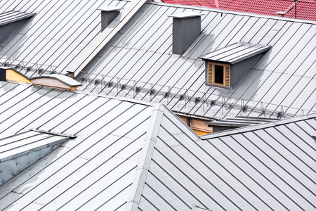 chimney corner: wet new metal grey roofs of city houses viewed from above