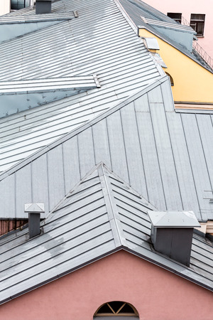 chimney corner: new grey metal gable roof in the rainy day