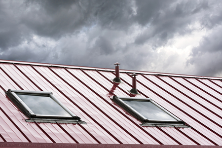 red metal: new grey metal roof with skylights against blue sky