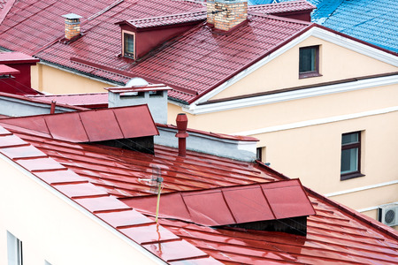 chimney corner: new red metal tiled roofs with chimneys and dormer windows