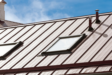 red metal: new metal roof with skylights against blue sky