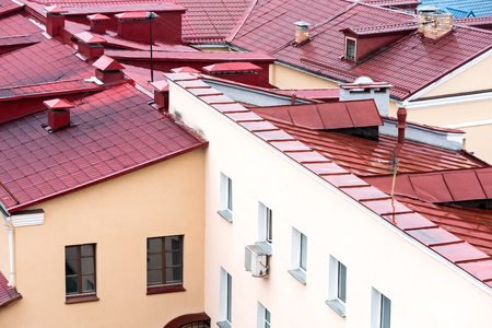 chimney corner: wet new metal tiled roofs of city houses viewed from above Stock Photo