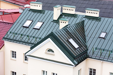 chimney corner: old house with new metal roof and skylights Stock Photo