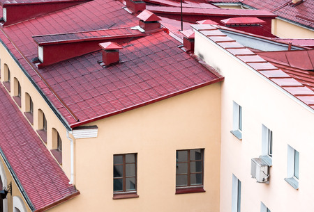 chimney corner: new red metal tiled roofs of old city houses top view