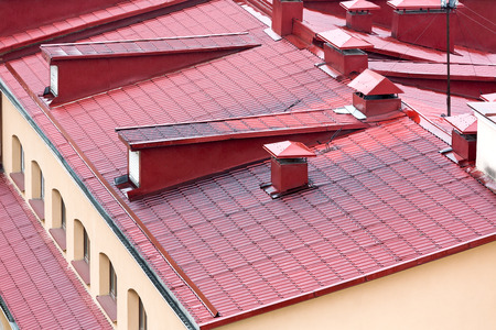 chimney corner: new red metal tiled roofs with dormer windows and chimneys