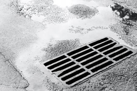 metal grate: metal sewer grate for drainage system on wet asphalt road
