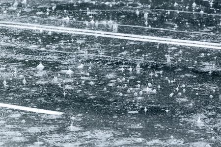 heavy rain: water splashes in puddle on asphalt road during heavy rain