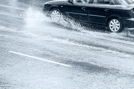 bad weather: car driving on wet city street during a downpour Stock Photo