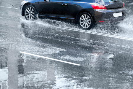 flooded street with car and puddles after heavy rain Archivio Fotografico